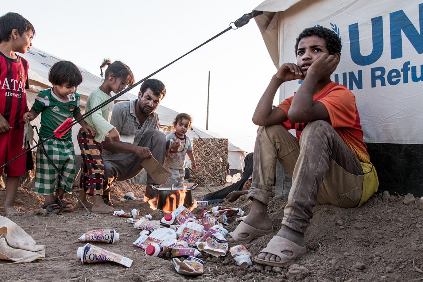 06_refugees-tent-boy-fire-cooking-litter-food